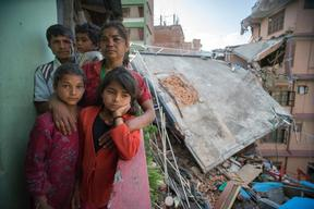 Twin sisters Jamuna, right, and Ganga, left, Nepali, 9, pose for a portrait  with their family in the quake-damaged apartment