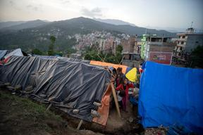 Jamuna Nepali, 9, center, with her mother and brother outside the tent