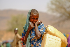 Displaced girl holding a jerrycan on her way to collect water from a unicef supported water point in Sotrony, North Darfur.