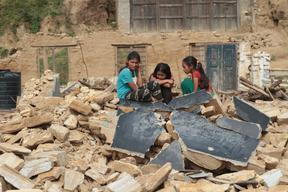 Three young girls sit on top of a destroyed blackboard in Shree Chaturmala Higher Secondary School in Muchowk