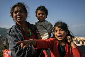 Jamuna Nepali, 9, right, with her mother and 4-year old brother Anuj in Charikot