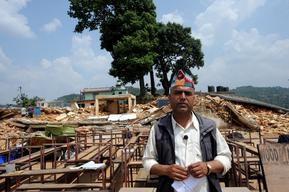 Teacher stands in front of the destroyed school