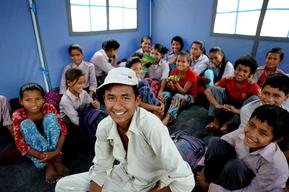 Ramesh Shrestha, 16, in white outfit smiles inside the makeshift tent school of Shree Balephi Secondary school