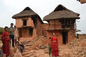 Residents stand in front of their damaged houses in Sitalpati