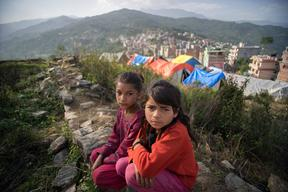 Twin sisters Jamuna, right, and Ganga Nepali, 9, pose for a portrait in the tent camp for earthquake-displaced people