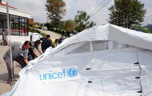 Staff members of Spinal Injury Rehabilitation Center and local police set up UNICEF-provided tent