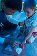 A young boy helps a younge boy complete a jigsaw puzzle of a fish at a UNICEF-supported child-friendly space in Syuchatar