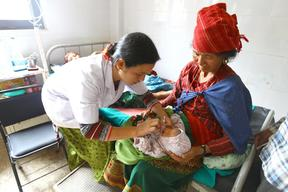 Staff Nurse Charu Thapa Magar knots the string of the traditional headwear of a newborn at the district hospital in Trishuli