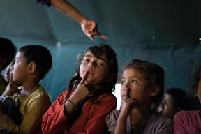 Jamuna Nepali, 9, (center, red) and other children attend a UNICEF-supported Child Friendly Space