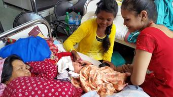 Newborn with 2 proud sisters & mom at UNICEF-sptd Patan Hospital