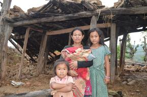 Chitra Kumari Magar, 27, holds her three-week-old daughter in front of her damaged house in Kamala Mai