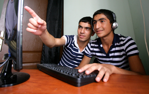 Two boys using at the screen using internet at the youth center