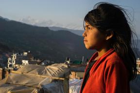 Jamuna Nepali, 9, looks towards the sunset from the tent camp for earthquake-displaced people
