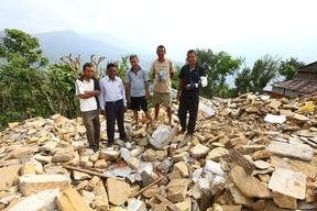 Five teachers stand among the rubble of destroyed Chaturmala Higher Secondary School in Muchowk