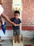 Rusuna Tamang, 4, holds his mother's hand while getting his height measured at UNICEF-supported out-patient therapeutic programme (OTP) clinic in Kamalamai